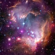 """""""הכנף של הענן המגלני הקטן"""". בתמונה מורכבת זו של הכנף, הנתונים של צ'אנדרה מוצגים בסגול, נתונים אופטיים מטלסקופ החלל האבל צבועים באדום, ירוק וכחול. נתונים של קרינה אינפרה אדומה מטלסקופ החלל שפיצר מיוצגים אף הם באדום."""