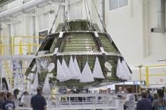 """עגורן מרים את מודול הצוות אוריון EFT-1 ממתקן האיחסון שלו להעברה להמשך ההרכבה במתקן הבדיקות והתפעול במרכז החלל קנדי של נאס""""א בפלורידה Credit: NASA/Frankie Martin"""