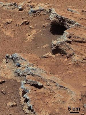 איזור במאדים בו זרמו מים. בתחתית התמונה הסלע הוטה הנראה כמו מדרכה שבורה - עדות לזרימת מים במקום