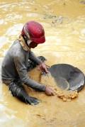 כורה מסנן זהב במכרה בתאילנד. צילום: Giambra / Shutterstock.com