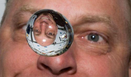 """האסטרונאוט קלייטון אנדרסון צופה בטיפת מים ובה השתקפותו במעבורת החלל דיסקברי. לכידות המים במיקרו כבידה שונה מאשר בכדור הארץ. צילום: נאס""""א"""
