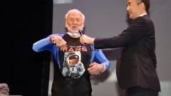 """האסטרונאוט באז אלדרין מציג חולצה ובה קריאה לצאת למאדים ותמונת סלפי שצילם בחלל ב-1966. צילום: ישראל בן אלי, לע""""מ"""