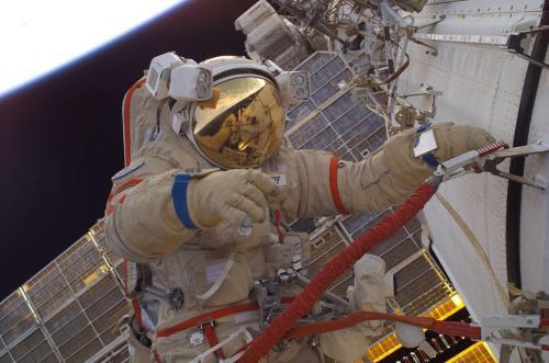 אסטרונאוט אמריקאי לבוש בחליפת אורלן רוסית, בתחנת החלל הבינלאומית, 2005. צילום: NASA/Sergei Krikalev.