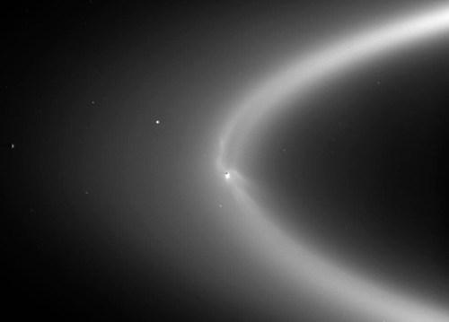 אֶנקֶלַדוּס (במרכז) כפי שהוא נראה ממרחק של שני מיליון קילומטרים. הירח משובץ בטבעת E של שבתאי, הנוצרת מתמרת הקרח שהוא פולט. מקור: NASA/JPL/Space Science Institute.