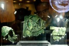 מבקרים מתבוננים בשבר של מנגנון אנטיקיתרה בן 2,100 שנה, שמעריכים כי הוא מכשיר המחשוב המכני המוקדם ביותר ששרד. התמונה צולמה במוזיאון באתונה ביוון. צילום: shutterstock