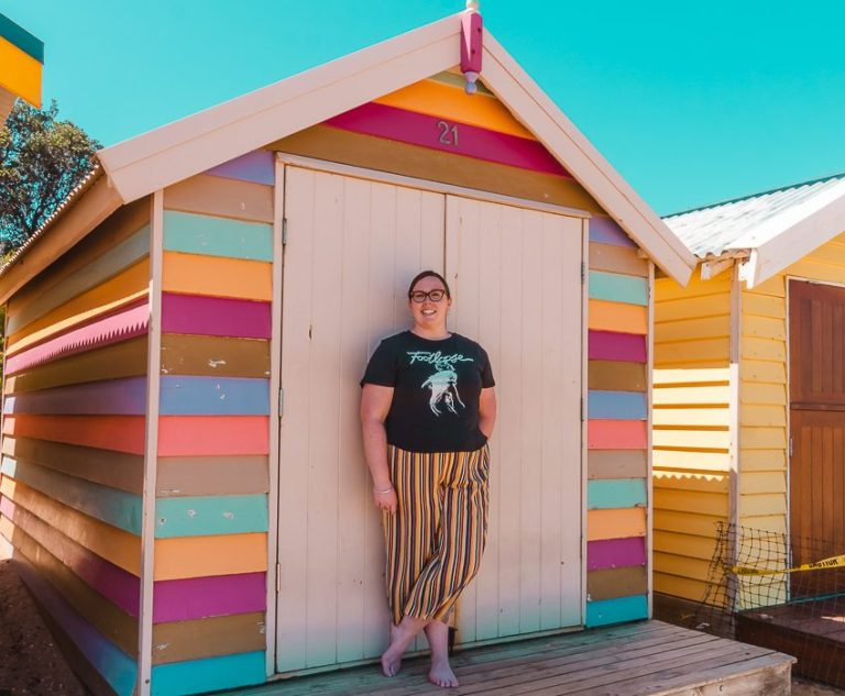 Standing in front of a pastel striped beach hut at the Brighton Bathing Boxes in Melbourne, Australia - one of the best free things to do in Melbourne!