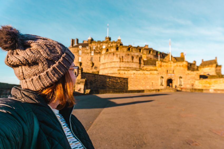 Side profile photo of myself looking towards Edinburgh Castle, glowing in the sunrise light.