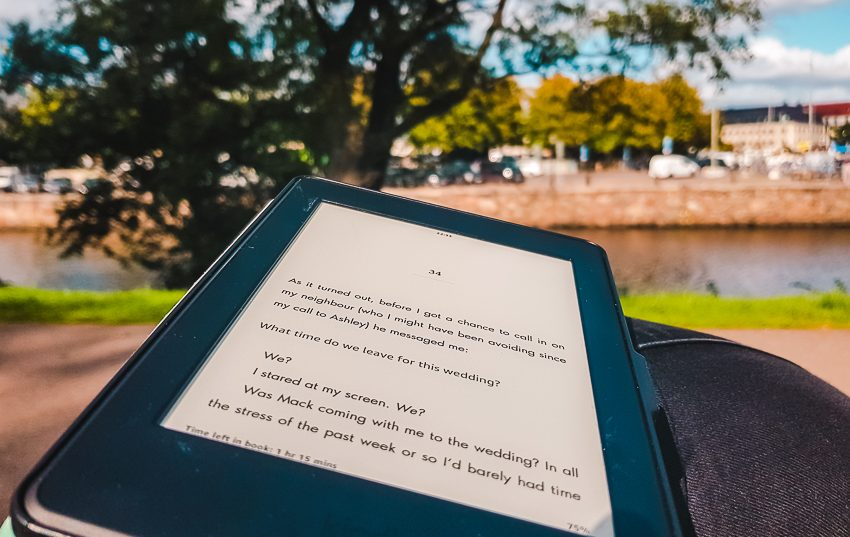 Reading my Kindle on a bench beside the river in Gothenburg, Sweden