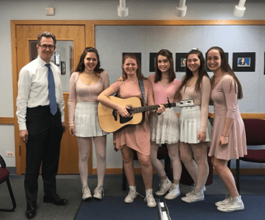 Superintendent, Dr. Bruce Law, enjoys the harmonies of the Singing Valentine group that consisted of Emily Goggin, Elisa Fridholm, Jordan Cibinski, Emily Condon, and Hannah Fuechtman, all sophomores.