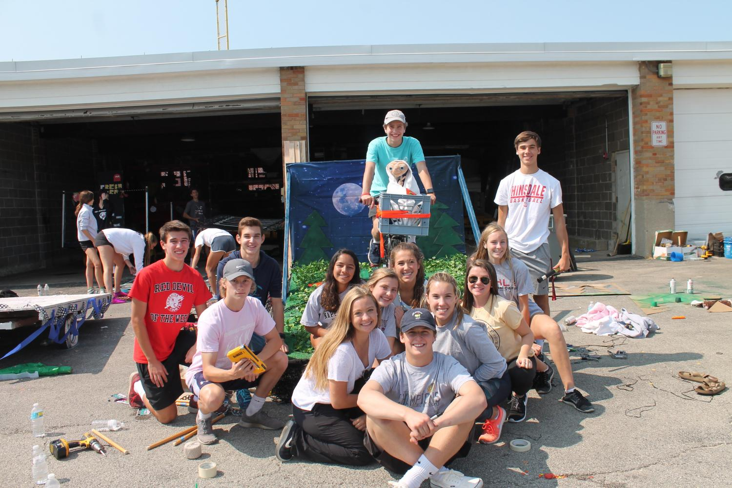 The junior class board poses next to their completed E.T. homecoming float.