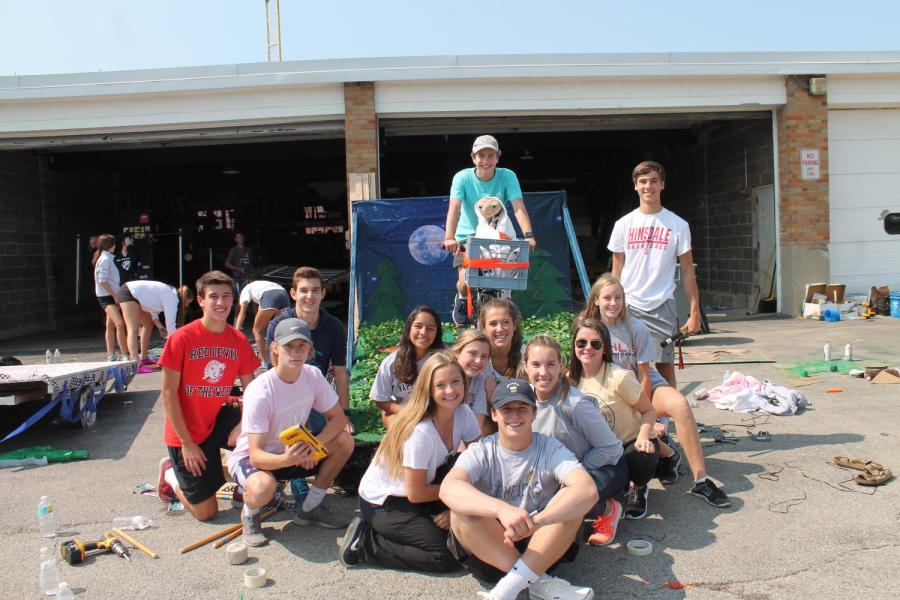 The+junior+class+board+poses+next+to+their+completed+E.T.+homecoming+float.
