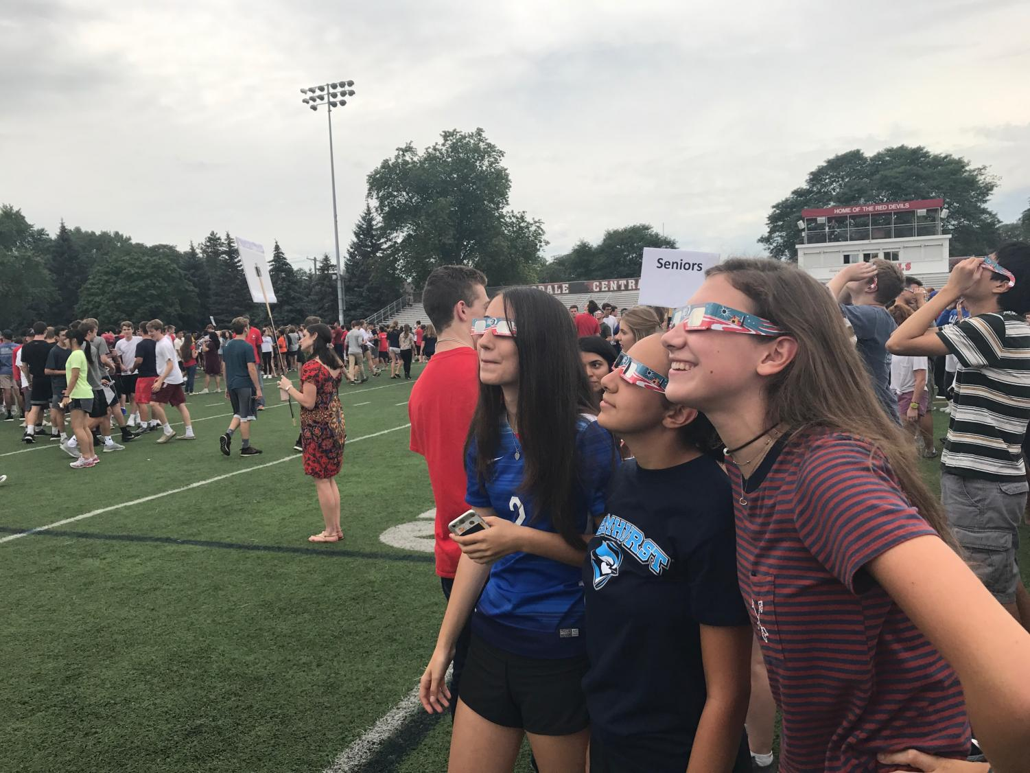 Seniors Elaine Carter, Jacinda Eskander, and Kerri Kenney watch the solar eclipse on the football field.