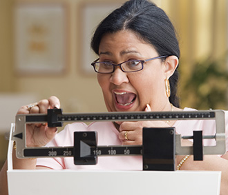 Shocked woman weighing herself