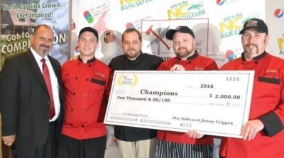 Team Vidalia Boom shows off the $2,000 grand prize and their red chef jackets after taking home first place in the Got to Be NC Competition Dining Series.