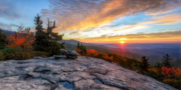 The sun rises on Beacon Heights (MP 305.2 on the Blue Ridge Parkway), as autumn foliage complements the hues of dawn. According to Dr. Howard Neufeld, Fall Color Guy and professor of biology at Appalachian State University, this coming week could be the best time to visit high-elevation spots on the Blue Ridge Parkway, since they peak earlier than lower elevations. Photo by Skip Sickler | Grandfather Mountain Stewardship Foundation