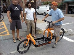 Don Cox (right) of Bald Guy Brew tries out his new cargo bike in front of Magic Cycles owner Mike Boone (left) and Ryan Puckett (middle). Photo by Matt Powell