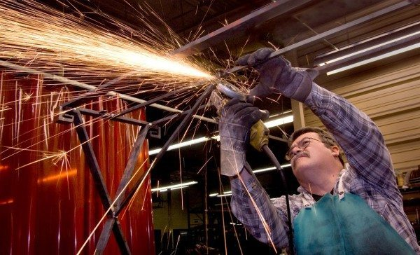 Ernie Houser trims a piece of steel on a custom console base he is building. Houser, a welder, has been with Charleston Forge since 1987, when the company was only three years old. Photo by Philip Holman / Charleston Forge