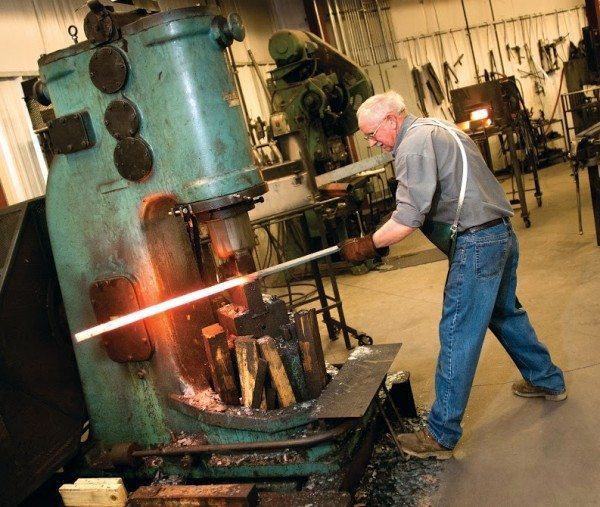 Ellis Cable, a blacksmith with Charleston Forge since 2000, hammers out a piece of raw steel to create a table leg. Every piece of Charleston Forge furniture is built by hand at its Boone, NC factory. (Photo by Philip Holman/Charleston Forge).