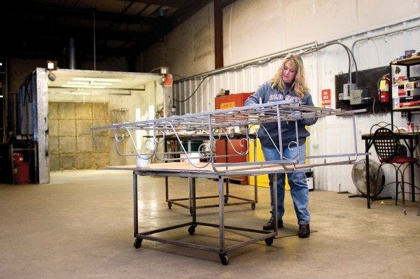 Dana Honeycutt applies one the company's nine hand-painted metal finishes to a steel baker's rack frame. All of Charleston Forge's 18 metal finishes start with a durable powder coat finish as their base. (Philip Holman/Charleston Forge)