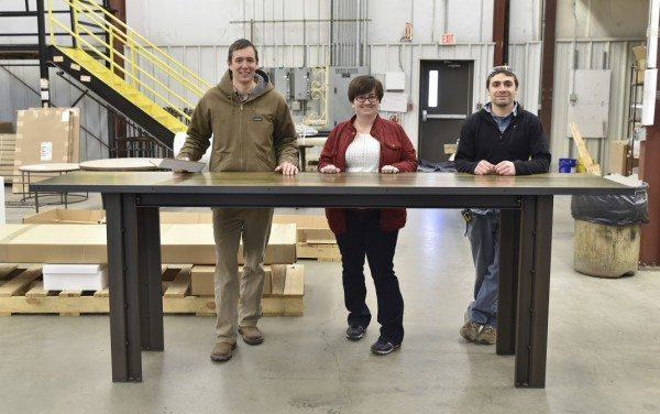 Charleston Forge General Manager, Andrew Beekman, left, Customs Engineer April Lyle, center, and Project Manager AJ Amero stand with one of the first Starbucks Community Tables at the cpmany's Boone, NC factory. (Photo by Karen Lehmann/Charleston Forge)