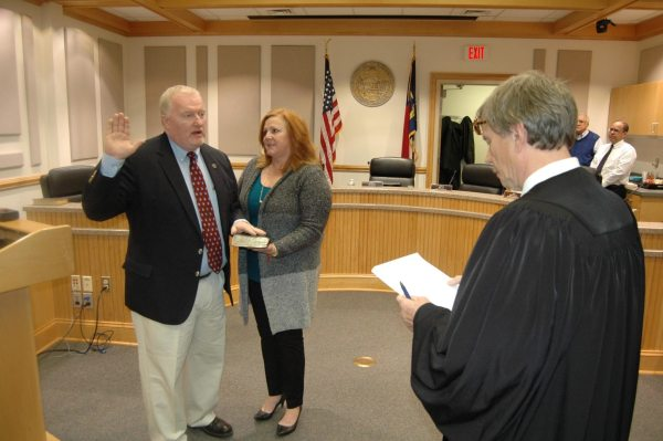 Republican Commissioner Perry Yates, with his wife Anne-Marie by his side, is sworn into office.