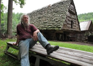 Eustace Conway rests on a wooden sledge in front of the horse barn at his Turtle Island Preserve in Triplett on June 27. (AP Photo/Allen Breed)