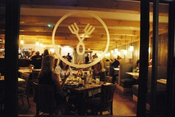 Guests enjoy dinner at Rustique during its opening in mid-April. Photo by Ken Ketchie.