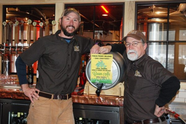 Lost Province owner and head brewer Andy Mason (right) and brewer Aaron Maas stand in front of the firkin of brew.