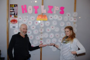 """Haircut 101 owner John Mena (left) and Bishop Glover stand with the wall of """"Hot Lips."""" Photo by Ken Ketchie"""