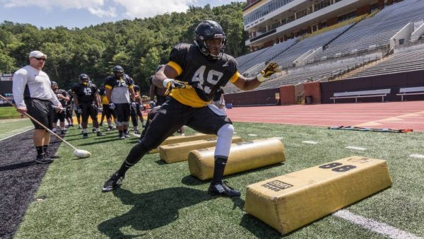 Senior defensive end Ronald Blair (49) completes a drill under the watchful eye of defensive line coach Mark Ivey (right). Photo courtesy App State Athletics