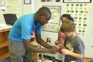 Godfrey Masauli helps Aidan Styron with his kite.