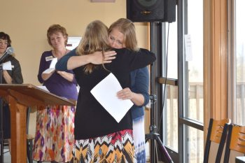 A local woman receives hugs and support after sharing her personal story of life-changing experience at Hospitality House.