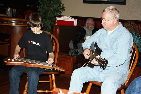 The young and the young-at-heart: 13-year-old Liam Purcell plays the dulcimer while John Payne plays his 1935 Kalamazoo guitar.