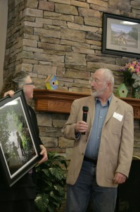 Kathy Parham presents Jim Atkinson with framed photo by Megan Long. Photo by Jennifer Spell