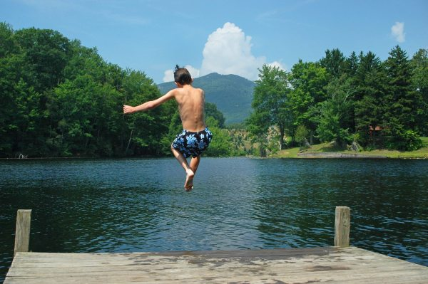 Banner Elk TDA/Boy captured mid-air jumping off a deck into Wildcat Lake in Banner Elk, North Carolina on a summer day. Photo by Todd Bush.