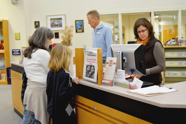 Employees at Watauga Library help local patrons check out new books at the circulation desk. Pictured behind the desk are Circulation Manager Randy Feimster (left) and County Librarian Monica Caruso.