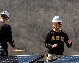 Evan Dubay, right, installs solar panels on a net-zero energy house that will be exhibited at the Solar Decathlon Europe 2014 in Versailles, France. Dubay is a senior appropriate technology major at Appalachian State University. Photo by Marie Freeman