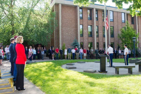 Chancellor Sheri N. Everts, left, stands with the speakers and attendees as Appalachian State University's ROTC cadre positions the flag during a Memorial Day ceremony. Photo credit: Marie Freeman.
