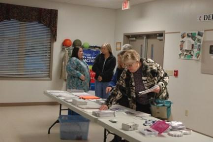Volunteers grab paperwork before the start of the meeting