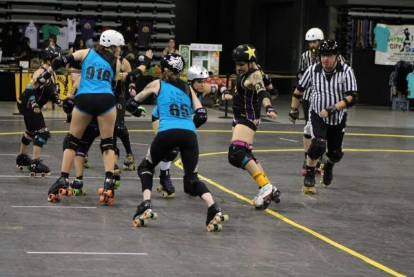 Appalachian Rollergirl, Jammer P.Y.T. (Patricia Ybanez) slipping by The Dominion Derby Girls from Virginia Beach, Virginia. Photo by Kevin Gordon.