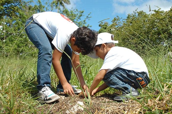 Dos niños, hijos de empleados, en plena labor de reforestación en Carlos Díaz, de Tamboril.