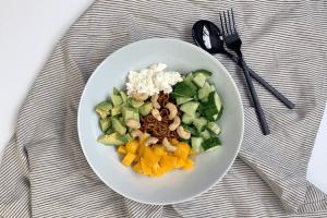 Lunchbowl met avocado, mango en cottage cheese