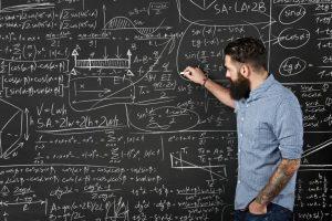 Bearded man draws formulas on a chalkboard