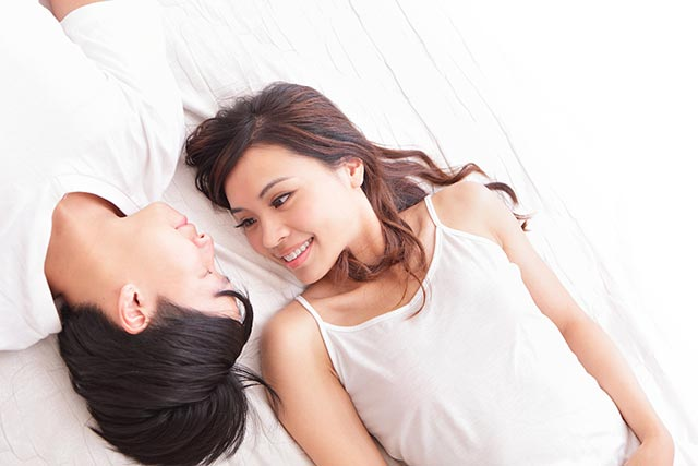 Young woman lying in bed and looking at her boyfriend besides her lovingly