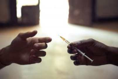 Drug abuse 29384630 - people abusing drugs, with african american man and caucasian guy sharing the same syringe to inject heroine