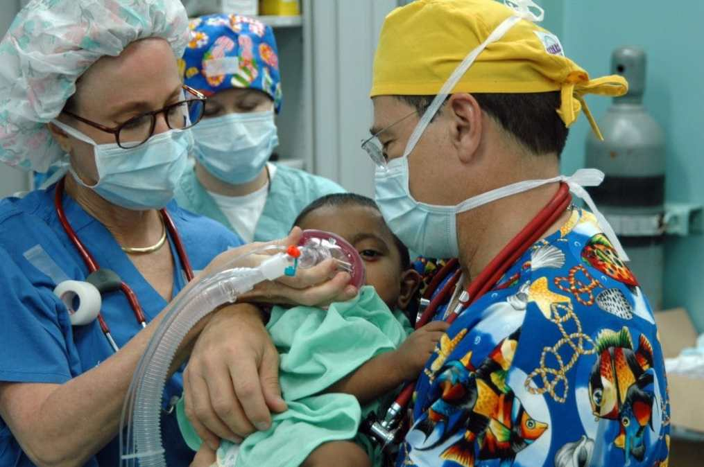 Public domain image. 060702-N-3532C-010 Chittagong, Bangladesh (July 2, 2006) Ð Operation Smile volunteers Janet Casabon Benowitz and Dr. Bill Pond anesthetize a young child before undergoing corrective plastic surgery on his cleft lip aboard U.S. Naval hospital ship USNS Mercy (T-AH 19), during the shipÕs visit to provide humanitarian and civic assistance to the people of Bangladesh. Mercy is on a five-month deployment to South Asia, Southeast Asia, and the Pacific Islands, having recently completed 24 days of humanitarian assistance to the people of the southern Philippines. The medical crew aboard Mercy will provide general and ophthalmology surgery, basic medical evaluation and treatment, preventive medicine treatment, dental screenings and treatment, optometry screenings, eyewear distribution, public health training and veterinary services as requested by the host nations. Mercy is uniquely capable of supporting medical and humanitarian assistance needs and is configured with special medical equipment and a robust multi-specialized medical team that can provide a range of services ashore as well as aboard the ship. The medical staff is augmented with an assistance crew, many of whom are part of nongovernmental organizations that have significant medical capabilities. U.S. Navy photo by Mass Communication Specialist Seaman Joseph Caballero (RELEASED)