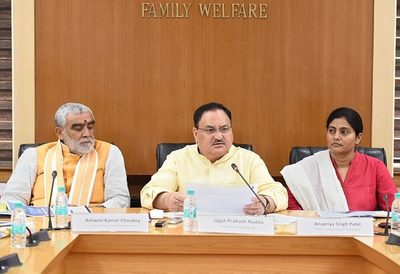 """em><strong>Union Minister for Health and Family Welfare J. P. Nadda (centre) attending a press conference concerning Ayushman Bharat. Image credit: Ministry of Health and Family Welfare (GODL-India) [GODL-India (https://data.gov.in/sites/default/files/Gazette_Notification_OGDL.pdf)] This file is a copyrighted work of the<a class=""""external text"""" href=""""https://www.india.gov.in/"""" rel=""""nofollow"""">Government of India</a>, licensed under the<a class=""""external text"""" href=""""https://data.gov.in/sites/default/files/Gazette_Notification_OGDL.pdf"""" rel=""""nofollow"""">Government Open Data License - India (GODL)</a>. This file or its source was published by Press Information Bureau on behalf of Ministry of Health and Family Welfare, Government of India under the ID<a class=""""external text"""" href=""""http://pib.nic.in/newsite/photo.aspx?photoid=123776"""" rel=""""nofollow"""">123776</a>and CNR 111225.<small>(<a class=""""external text"""" href=""""http://pibphoto.nic.in/photo//2018/Mar/l20180322123776.jpg"""" rel=""""nofollow"""">directlink</a>).</small></strong></em>"""