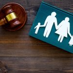 Family law, surrogacy, family right concept. Child-custody concept. Family with children cutout near court gavel on dark wooden background top view. Image credit: Oksana Mironova / 123rf