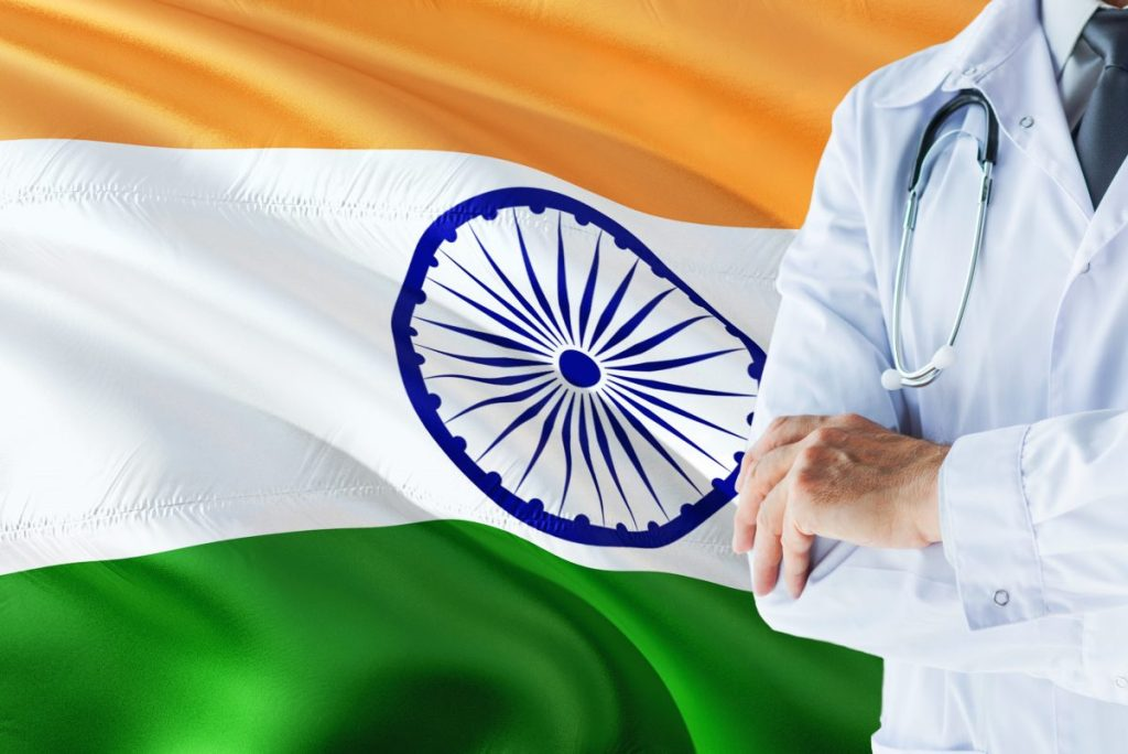 Indian Doctor standing with stethoscope on India flag background. National healthcare system concept, medical theme.