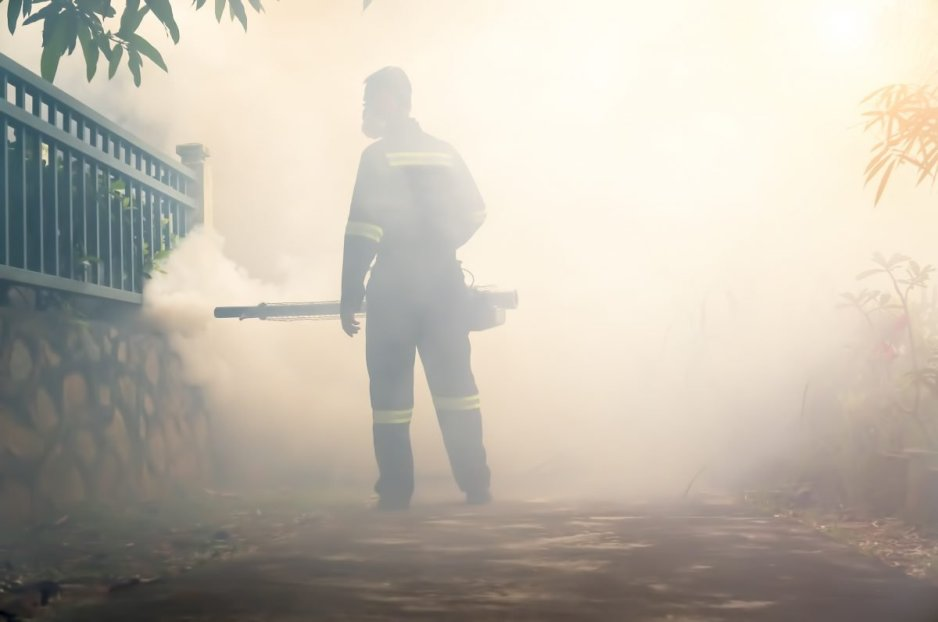 Action on dengue. Stock Photo - Environmental health operator fogging using chemical for dengue control outbreak with sunlight effect. Motion blur effect. Concept.